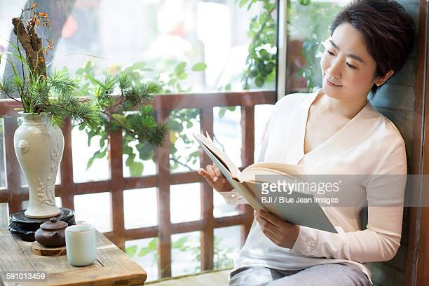 Mid adult woman reading book in tea room