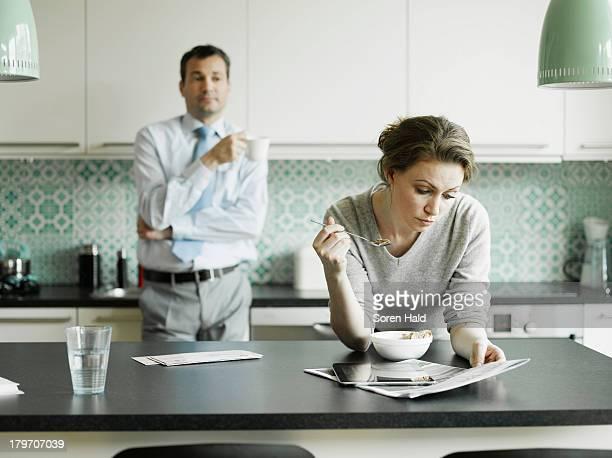 mid adult woman reading document over breakfast in kitchen - relatieproblemen stockfoto's en -beelden