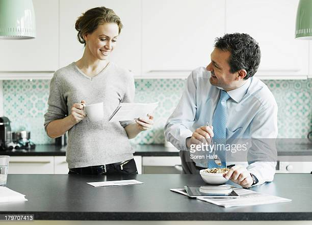 Mid adult woman reading document over breakfast with husband