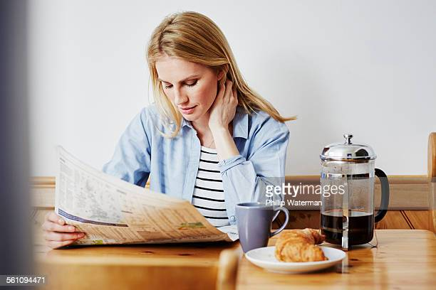 Mid adult woman reading newspaper