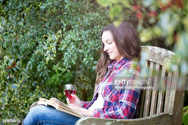 Mid adult woman reading on garden bench at Thornbury Castle, South Gloucestershire, UK
