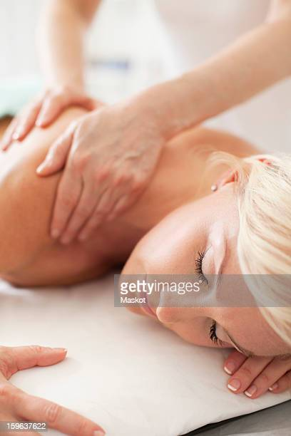 Mid adult woman receiving a shoulder massage at health spa