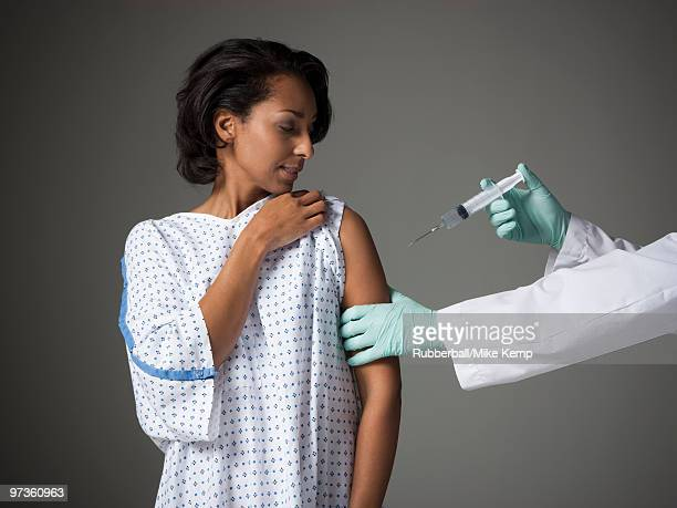 Mid adult woman receiving injection
