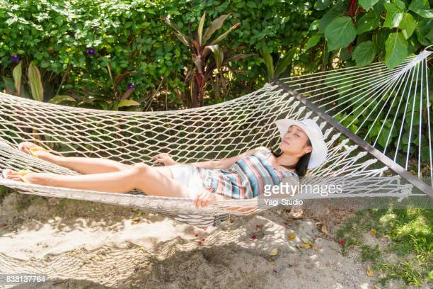 mid adult woman relaxing in the hammock at resort hotels in guam - guam stock pictures, royalty-free photos & images