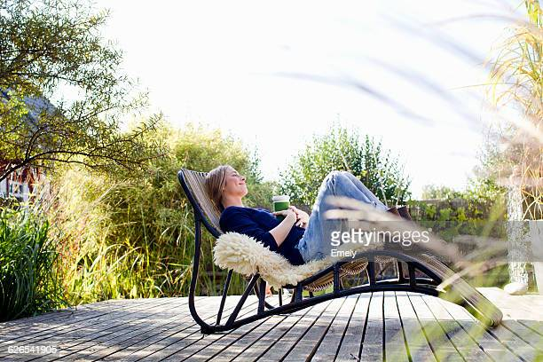 mid adult woman relaxing on lounge chair on wooden decking - cadeira recostável - fotografias e filmes do acervo