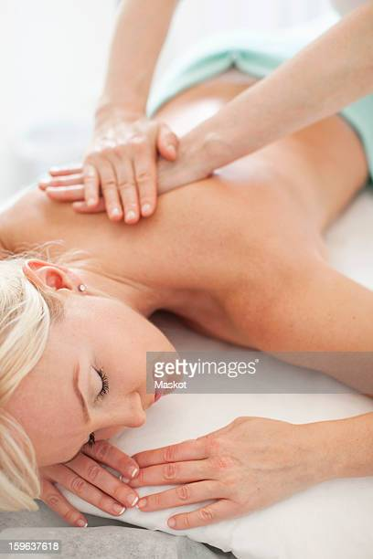 Mid adult woman relaxing with eyes closed with masseur giving a massage