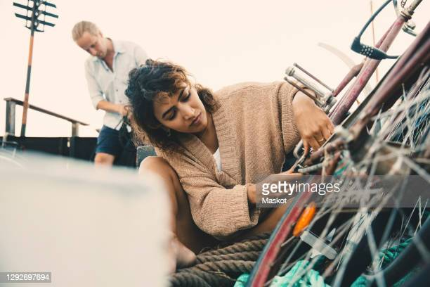 mid adult woman repairing bicycle while boyfriend in background at houseboat - repairing stock pictures, royalty-free photos & images