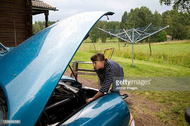 mid adult woman repairing vintage car - vintage auto repair stock pictures, royalty-free photos & images