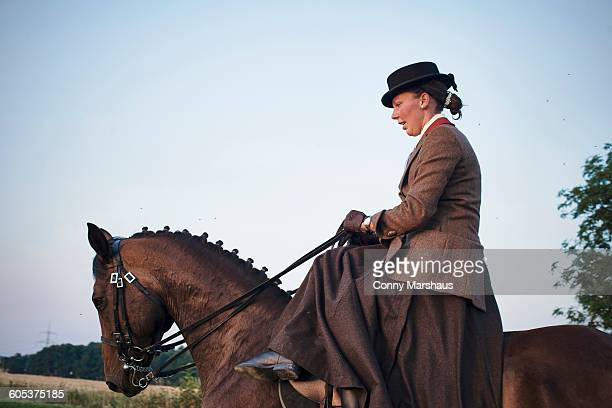Mid adult woman riding and training dressage horse in field