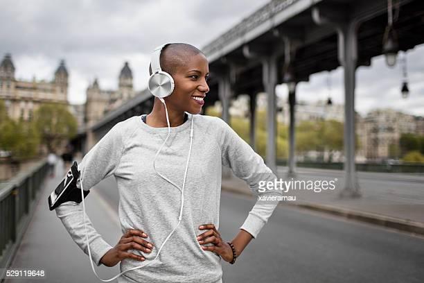 Mid adult woman runner listrening to headphones in Paris