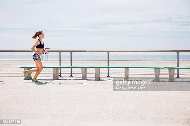 mid adult woman running beside beach - rockaway peninsula photos et images de collection