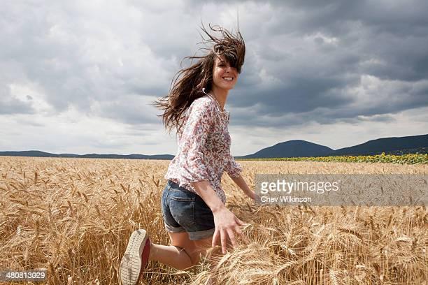 Mid adult woman running through wheat field