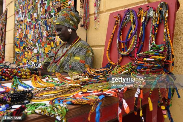 mid adult woman selling colorful personal accessories at market stall - senegal fotografías e imágenes de stock