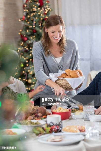 mid adult woman serves bread at family christmas dinner - mid adult stock pictures, royalty-free photos & images