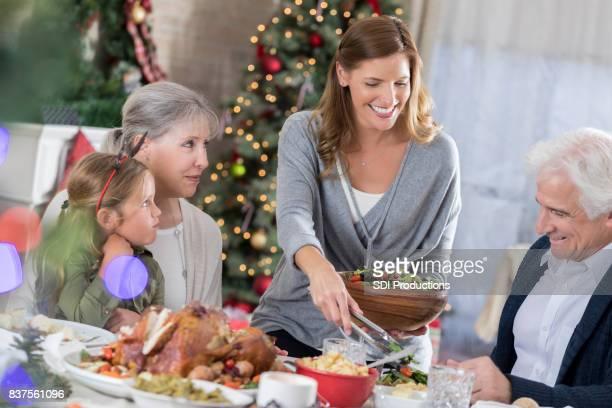 Mid adult woman serves Christmas dinner