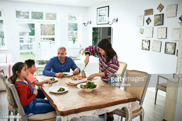 mid adult woman serving family dinner to husband and children - tavolo da soggiorno foto e immagini stock