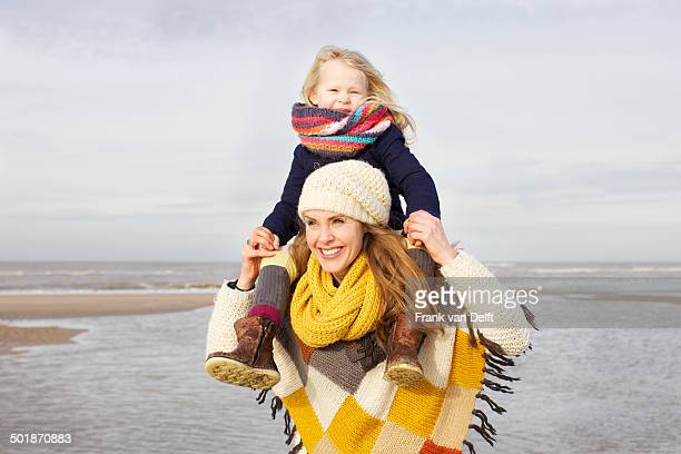 mid adult woman shoulder carrying daughter on beach, bloemendaal aan zee, netherlands - gemeinsam gehen stock-fotos und bilder