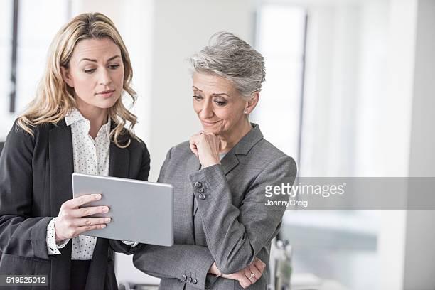 Frau mittleren Alters mit ältere Kollegen Digitaltablett