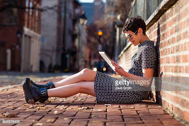 mid adult woman sitting against brick wall, using digital tablet - hitech mod a stock pictures, royalty-free photos & images