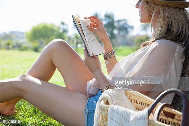 Mid adult woman sitting against tree, reading book