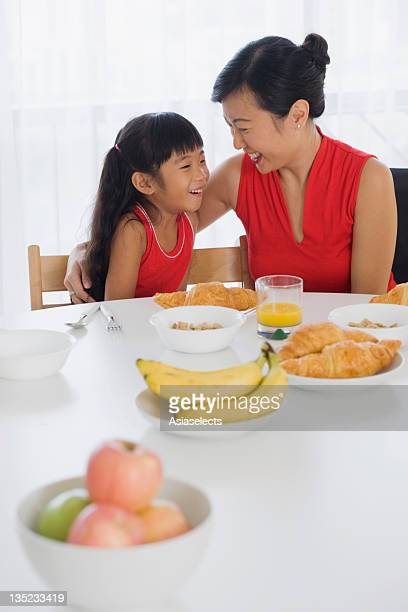 Mid adult woman sitting at a breakfast table with her daughter