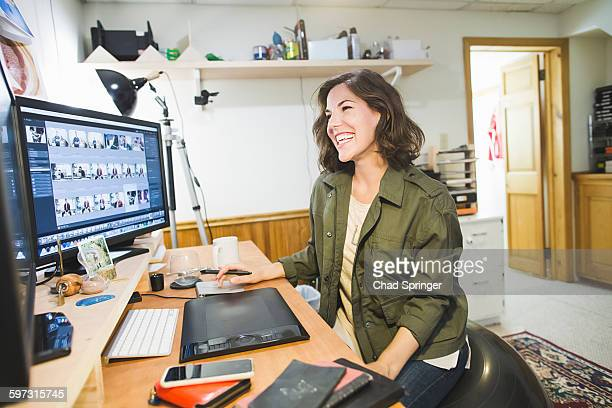 Mid adult woman sitting at desk, using graphics tablet, looking at computer screen