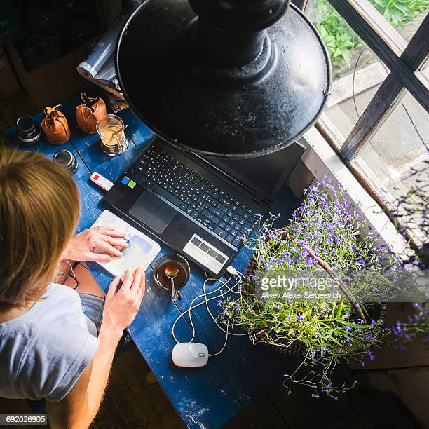 Mid adult woman sitting at desk, with laptop, looking at notebook, overhead view