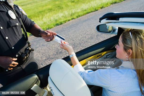 Mid adult woman sitting in a car giving her driver's license to a police officer