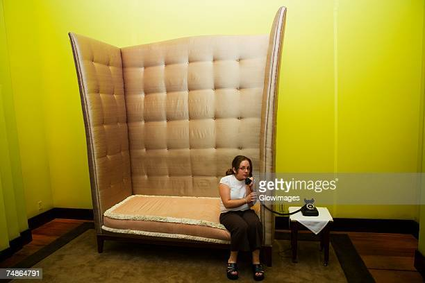 mid adult woman sitting in an armchair and talking on a rotary phone - tamanho desproporcionado - fotografias e filmes do acervo