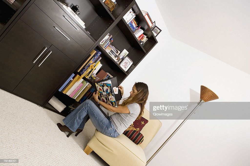 Mid adult woman sitting on a couch and reading a magazine : Foto de stock