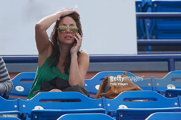 Mid adult woman sitting on bleachers and talking on a mobile phone