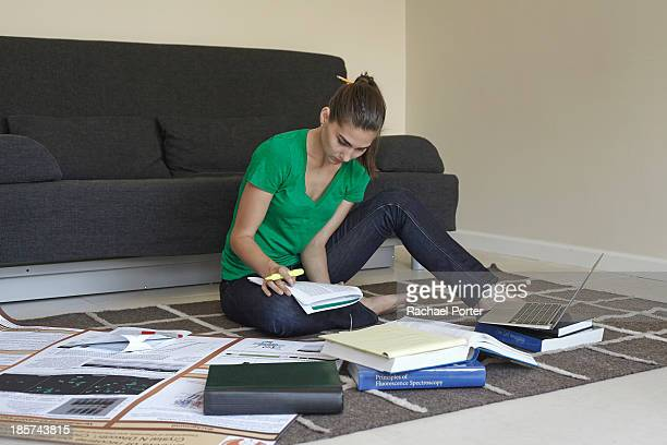 Mid adult woman sitting on floor studying