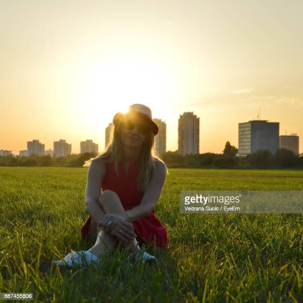 Mid Adult Woman Sitting On Grassy Field Against City During Sunset