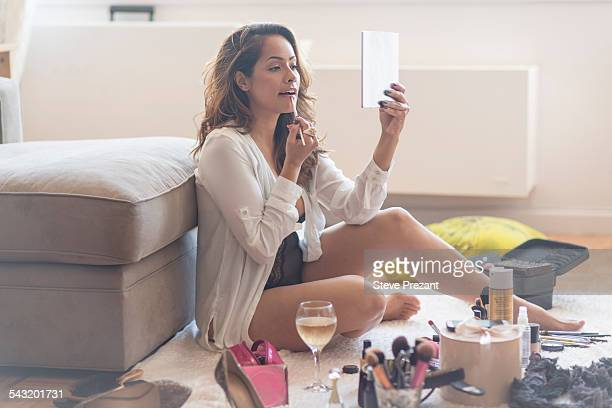Mid adult woman sitting on living room floor applying lipstick