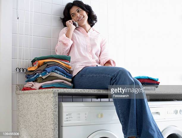 Mid adult woman sitting on washing machine and talking on phone