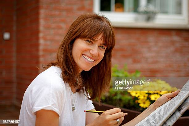 Mid adult woman sitting outdoors doing crossword, looking at camera, smiling