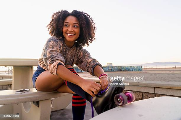 mid adult woman sitting outdoors, tying rollerskates - solo una donna di età media foto e immagini stock