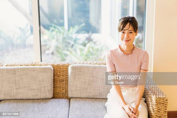 mid adult woman sitting sofa in hotel - one mid adult woman only stock pictures, royalty-free photos & images