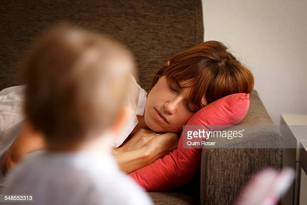Mid adult woman sleeping on sitting room sofa watched by toddler daughter