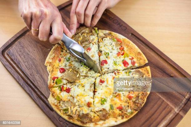 Mid adult woman slicing pizza