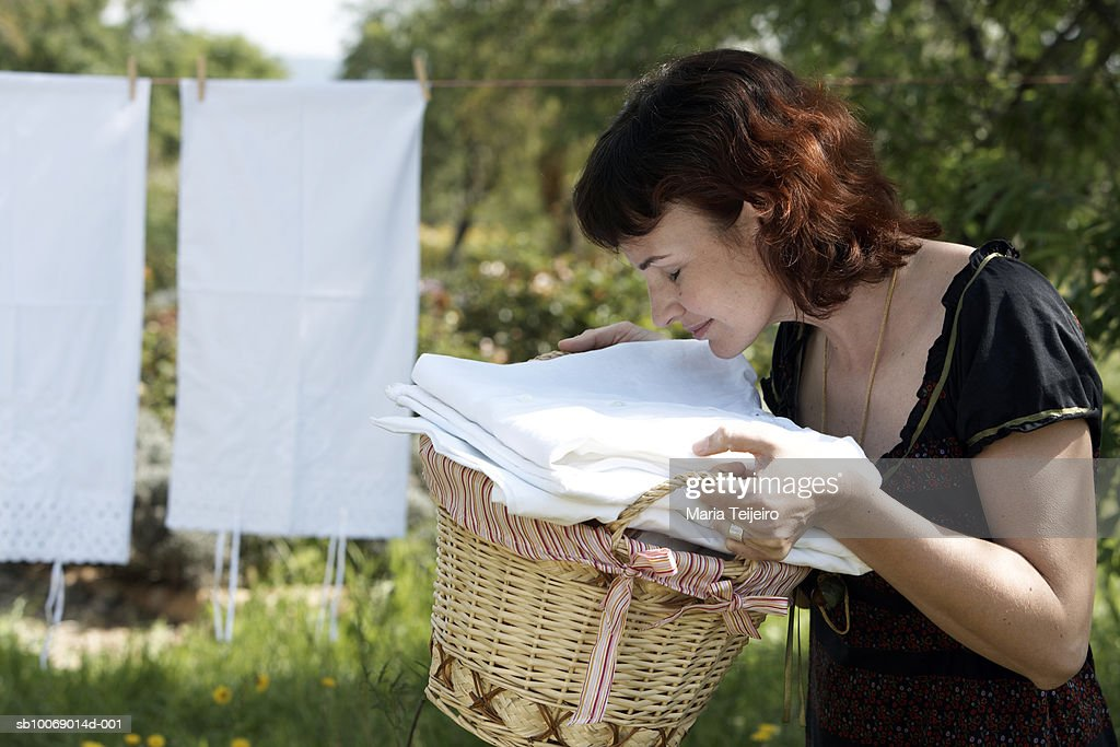Mid adult woman smelling fleshly washed clothes in garden : Stock Photo