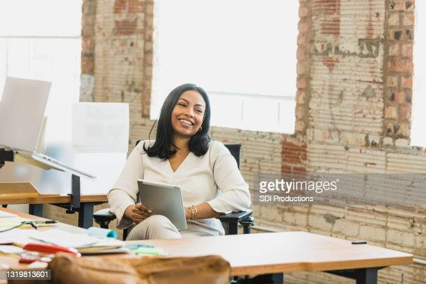 mid adult woman smiles while chatting with unseen person - hot desking stock pictures, royalty-free photos & images