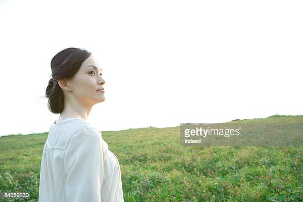 Mid adult woman smiling on grass field