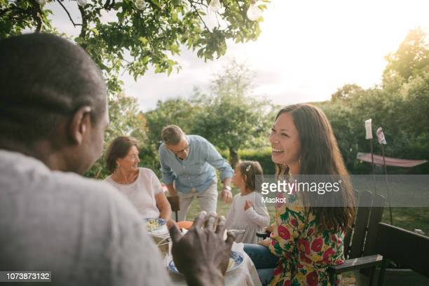 mid adult woman smiling while having lunch at table during garden party - mid volwassen mannen stockfoto's en -beelden