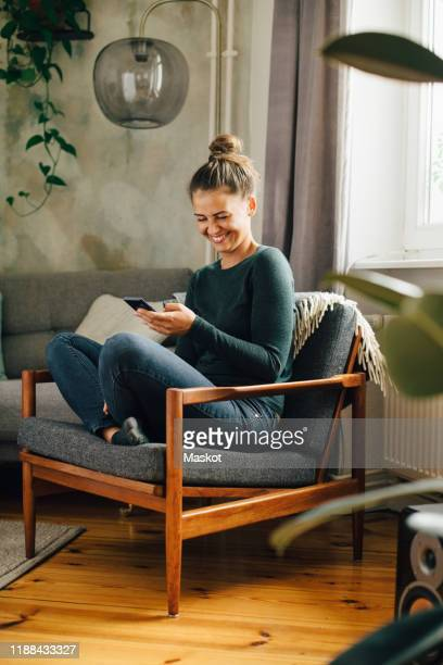 mid adult woman smiling while using mobile phone on armchair at home - behaglich stock-fotos und bilder