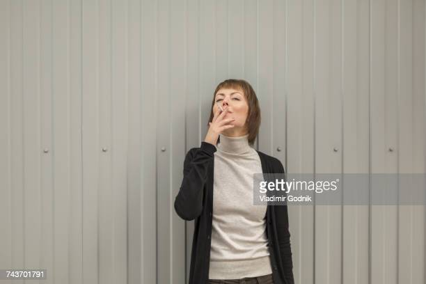 Mid adult woman smoking cigarette while standing against wall
