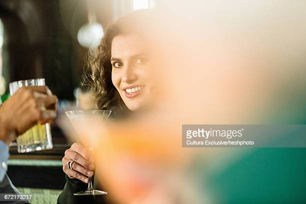 mid adult woman socialising in crowded recreational bar - heshphoto stock pictures, royalty-free photos & images