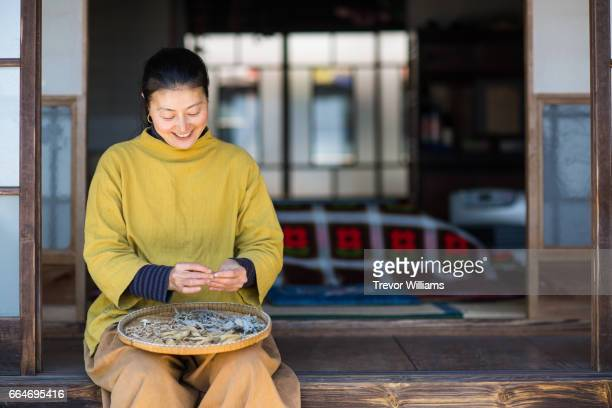 Mid adult woman sorting sun dried homegrown fruits and vegetables
