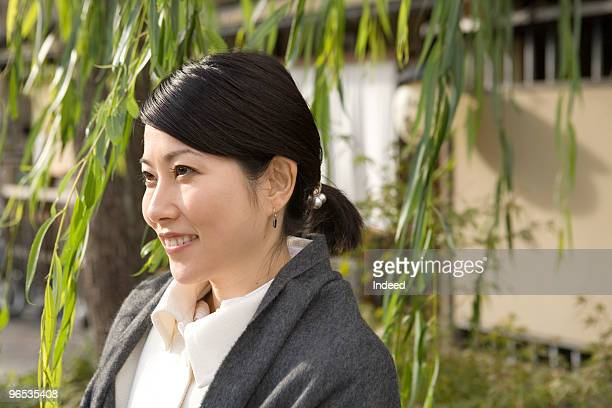 Mid adult woman standing beneath a willow, smiling