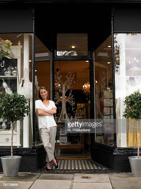 Mid adult woman standing in entrance to shop with arms crossed, smiling, portrait